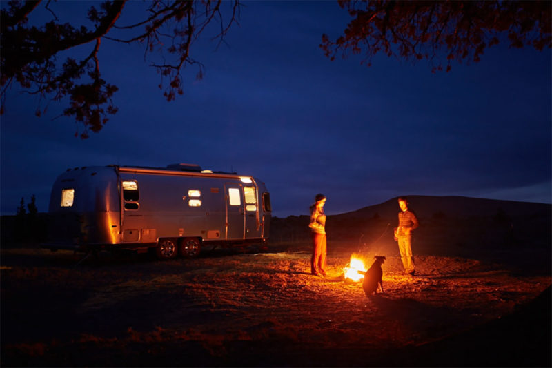 a couple hanging out by a campfire next to their airstream