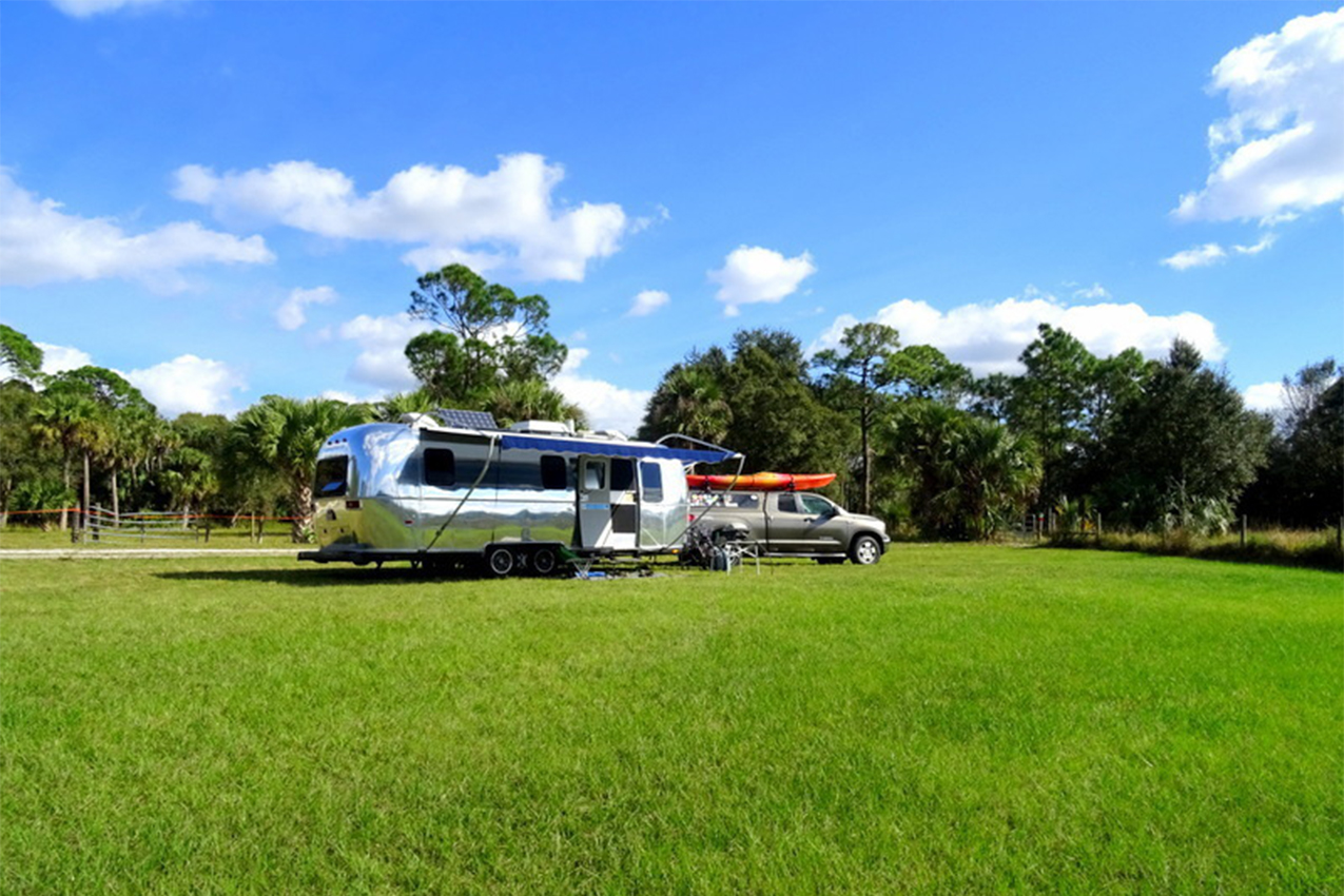 Shiny Airstream and truck with kayak on top parked in a green field.