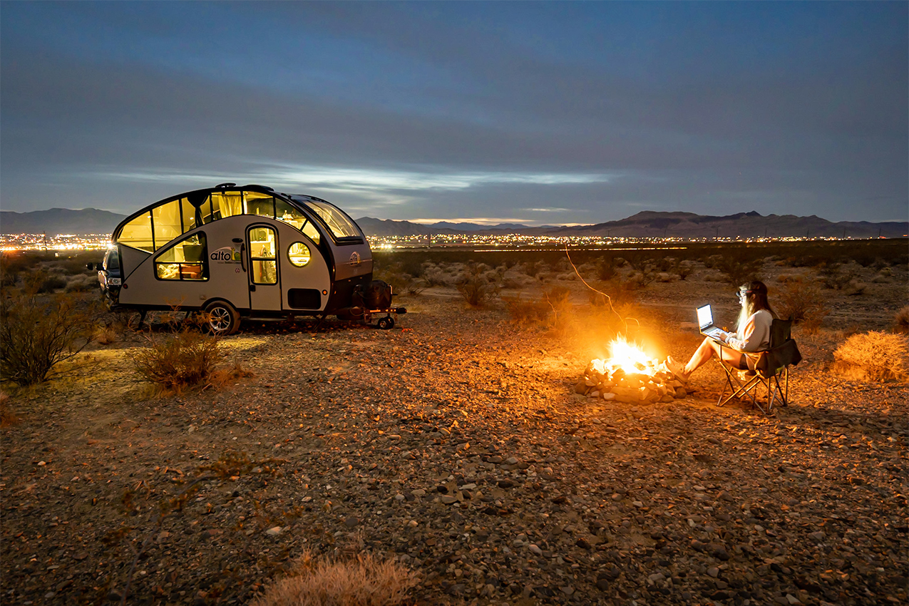 Teardrop camper and person sitting in front of campfire.