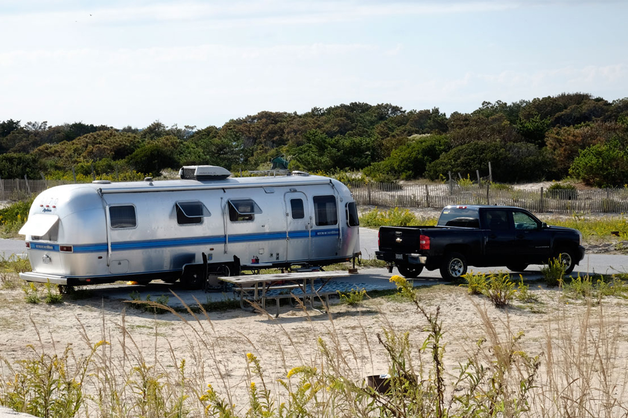 RV and truck parked near sand dunes.