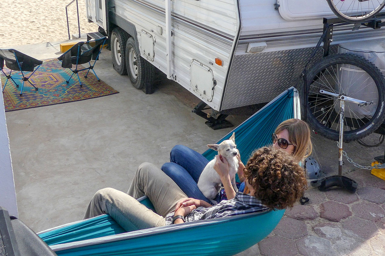 Couple and their dog sitting in a hammock outside their RV.