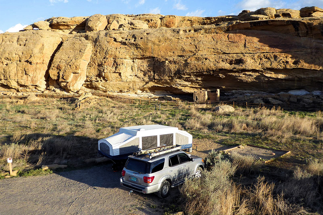 RV parked next to canyon rocks.
