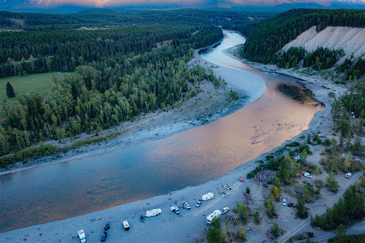 RVs parked along the banks of a river at sunset.