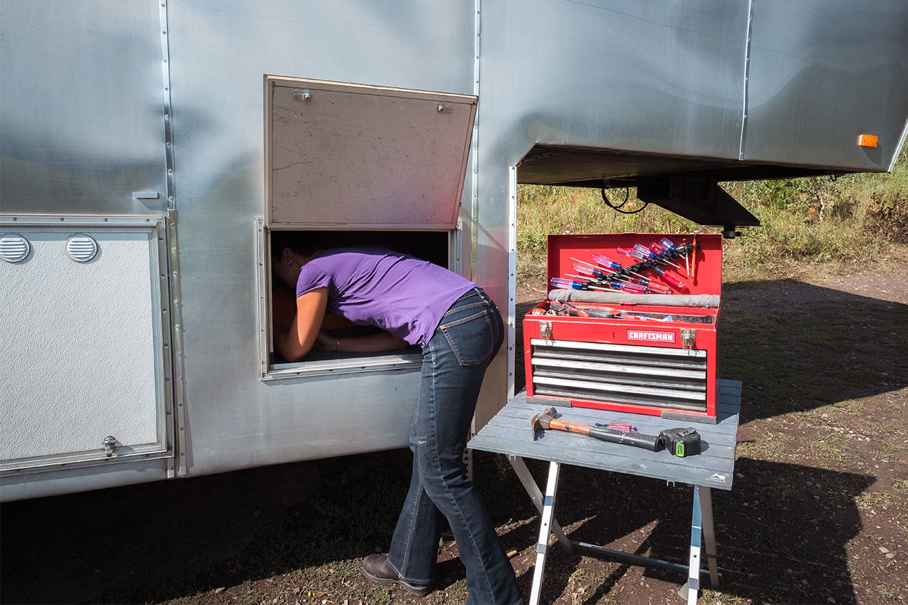 Woman working on RV with tools on table next to her.