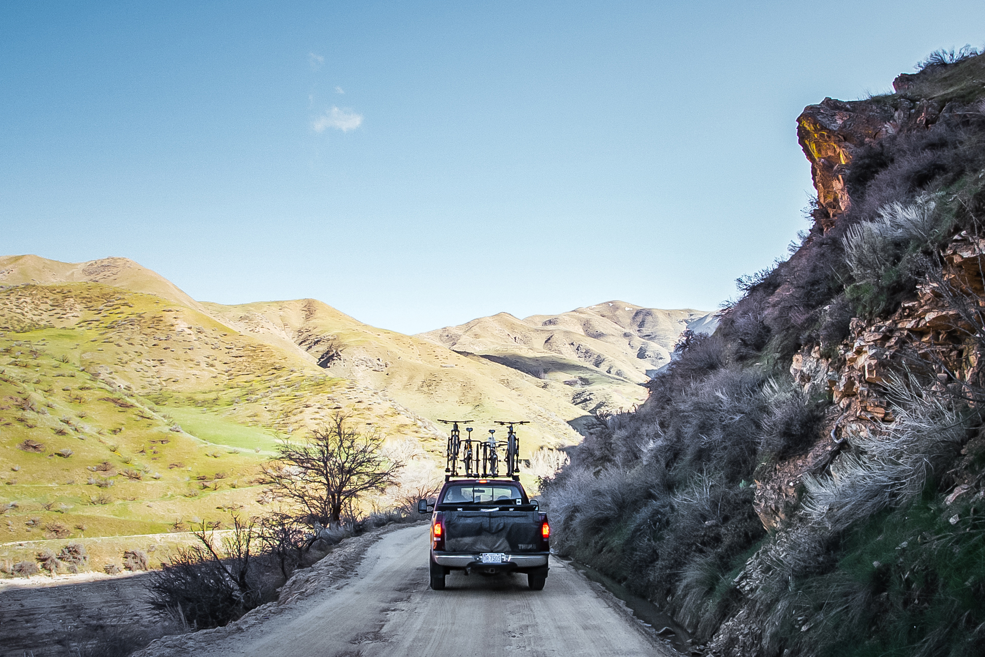 Truck with bikes on roof driving down gravel wall next to rock wall.