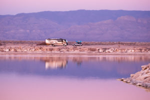 Pink sky and lake at sunset with class A and car parked on the shoreline.