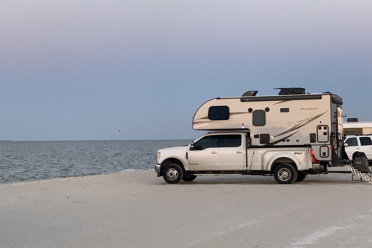 Truck camper parked on a beach.