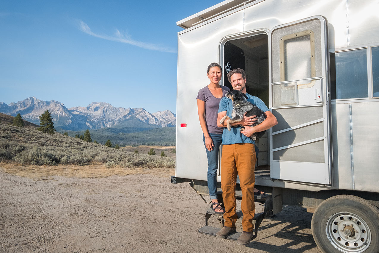 A couple and a dog standing in front of their silver RV.