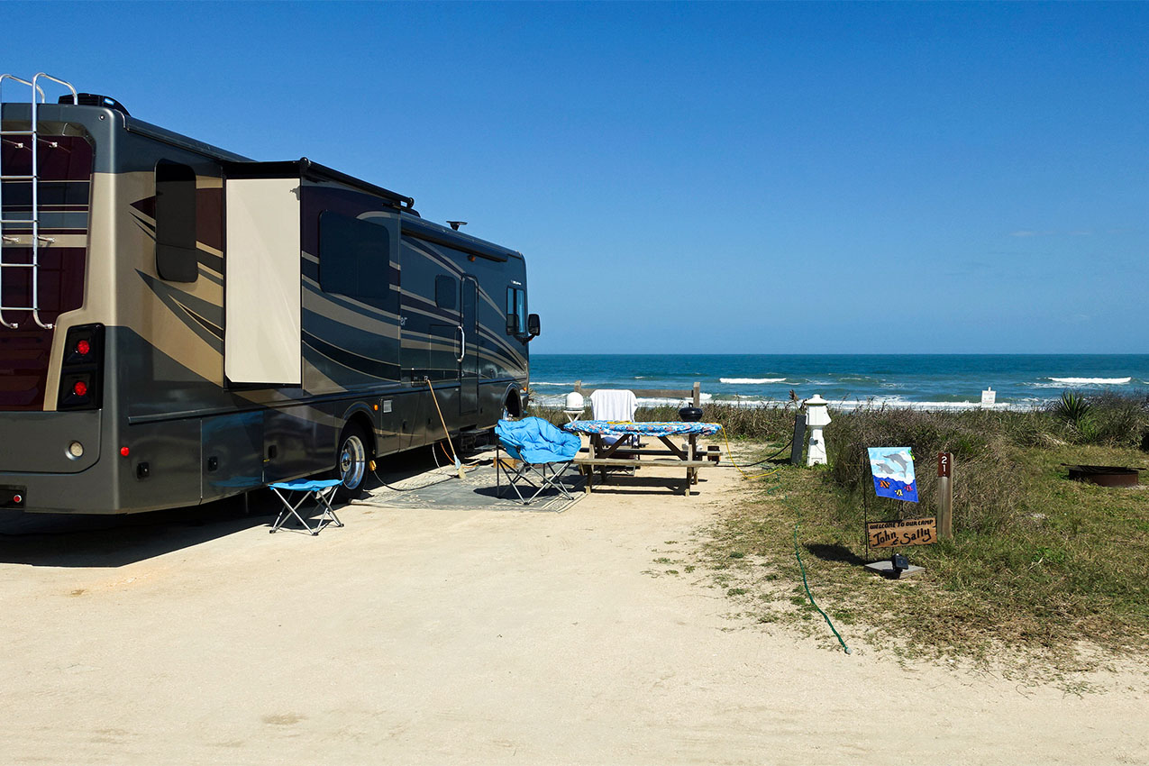 Class A with outdoor seating set up at campsite in front of ocean.