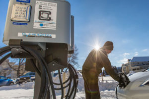 A man charging his electric vehicle in the snow at a charging station.