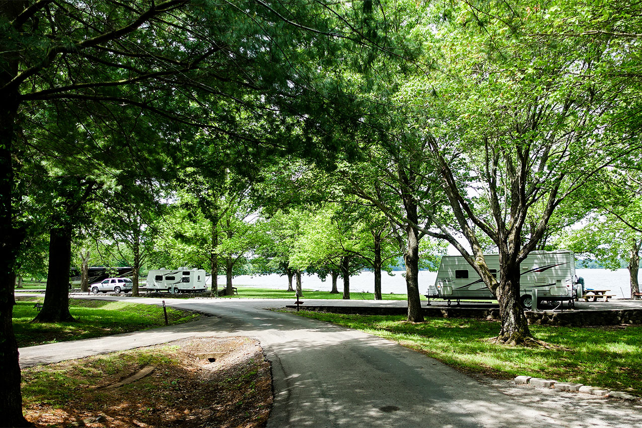 Two RVs parked in a campground under trees next to a lake.