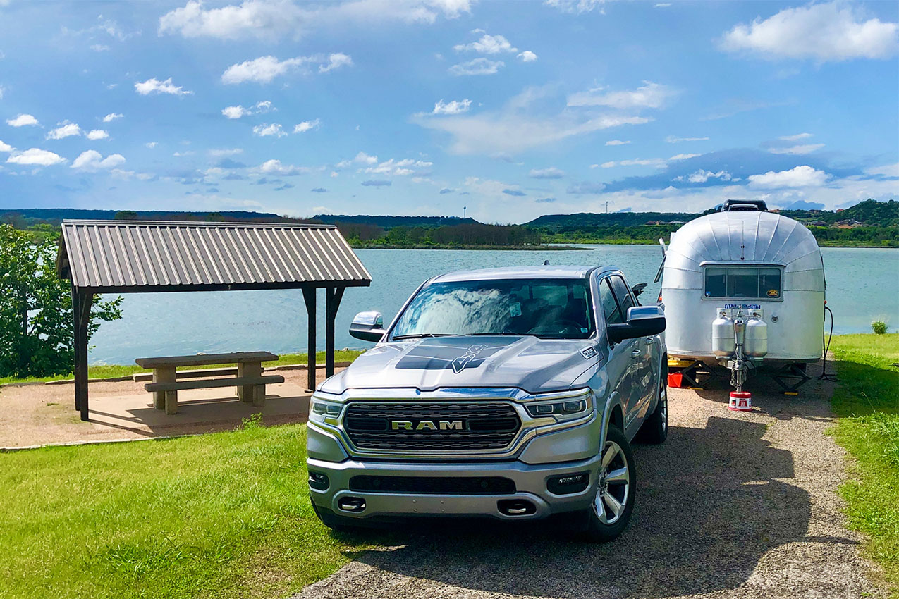 Truck and Airstream parked in front of a lake next to a covered picnic table.
