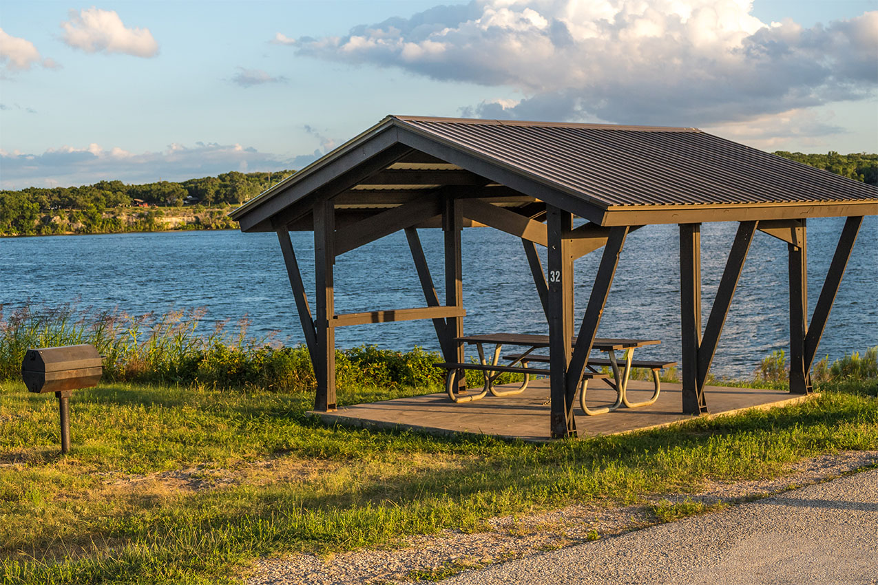 Covered picnic table and grill in front of a lake during golden hour.
