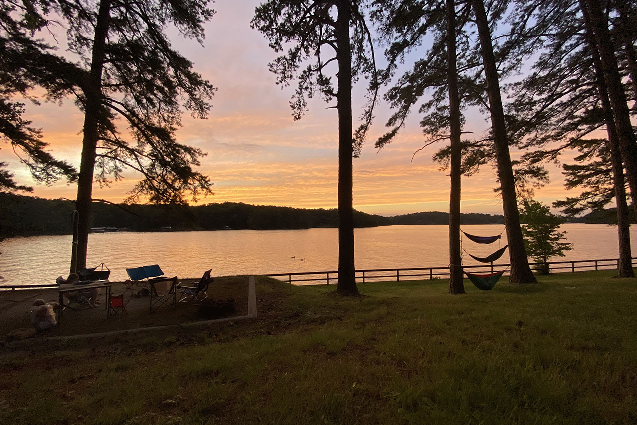 Silhouette of hammocks hanging between trees and camp chairs next to a lake during sunset.