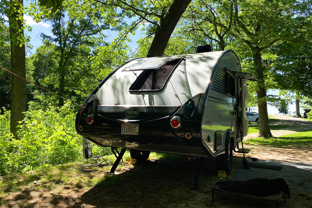 Teardrop camper parked in a heavily wooded campsite with a dog sleeping outside.