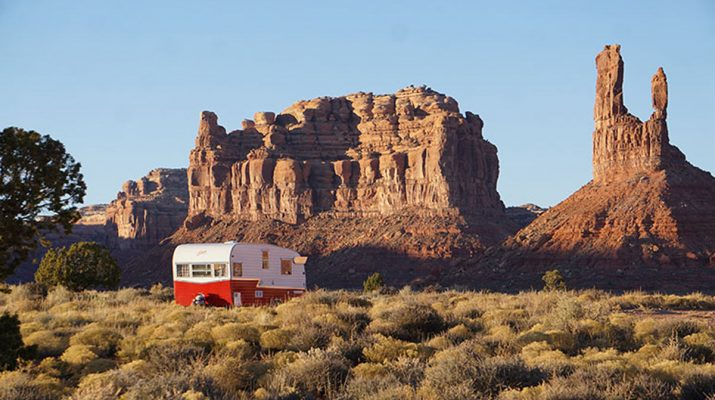 A cute red and white vintage Shasta travel trailer camping for free near a rocky mesa in the United States