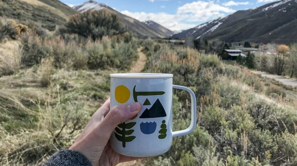 A hand holding a coffee cup with mountain view in the bacground