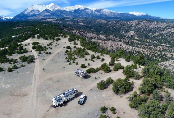 Rvs parked in a large open meadow with mountains in the background.